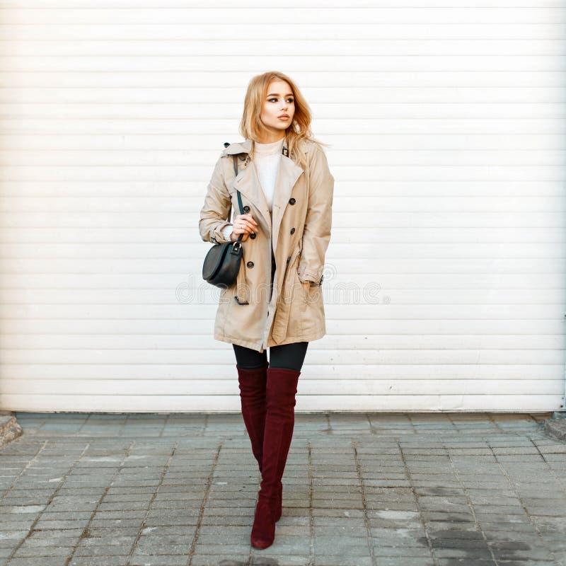 Hübsche Frau in einem modischen Mantel mit einer Handtasche und stilvoll stockbild