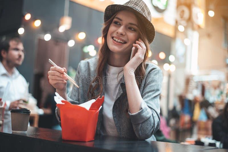 Hübsche Frau genießt die Unterhaltung auf Smartphone während der Mahlzeiten lizenzfreie stockbilder