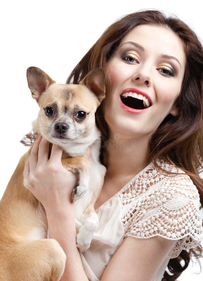 Hübsche Frau hält auf Händen einen kleinen Hund stockfotografie