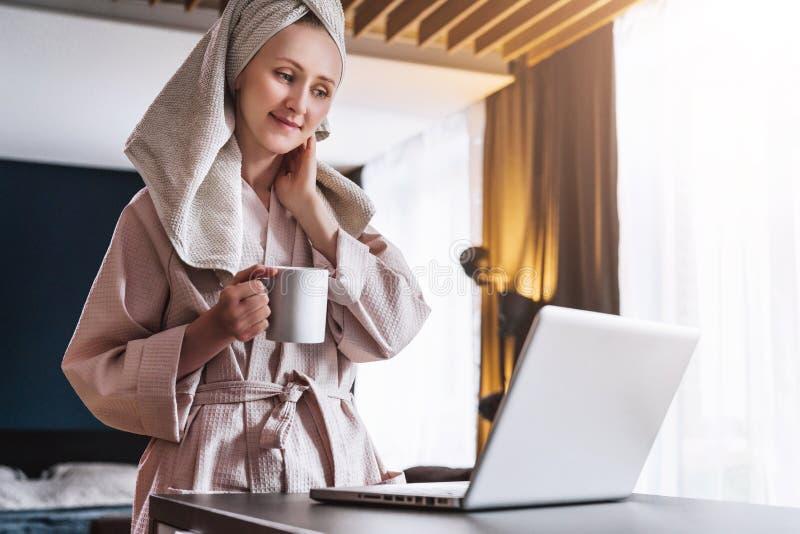 Hübsche Frau im Bademantel unter Verwendung des Laptops bei Tisch mit Partner im Hintergrund zu Hause in der Küche stockbild