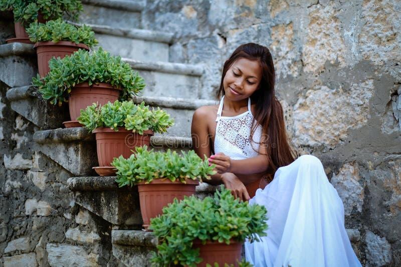 Hübsche Frau im ethnischen traditionellen Mittelmeerkostüm, das auf Steintreppe sitzt stockbild