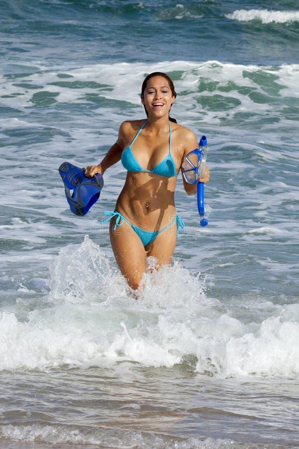 Hübsche Frau im gehenden Schnorcheln des hellblauen Bikinis stockbild