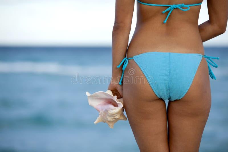 Hübsche Frau im hellblauen Bikini, der ein Oberteil hält stockbild