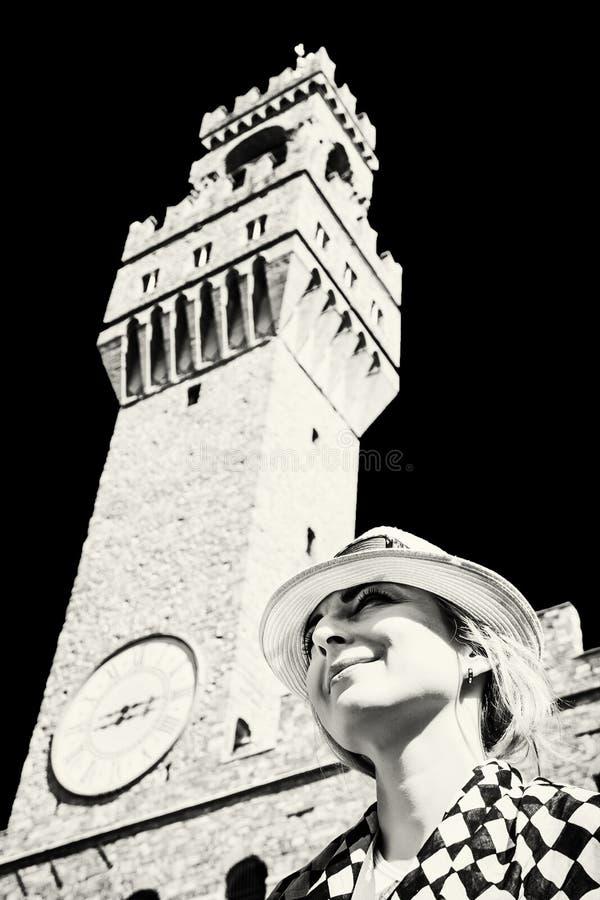 Hübsche Frau im Hut, der unter dem Palazzo Vecchio in Florenz aufwirft lizenzfreie stockfotos