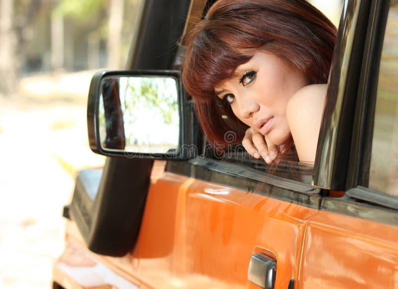 Hübsche Frau im orange Auto lizenzfreies stockbild