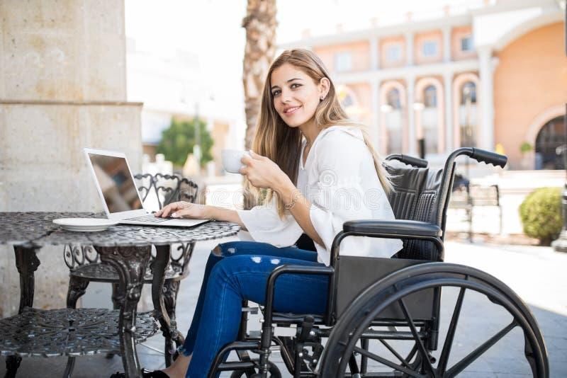 Hübsche Frau im Rollstuhl an einem Café lizenzfreies stockbild