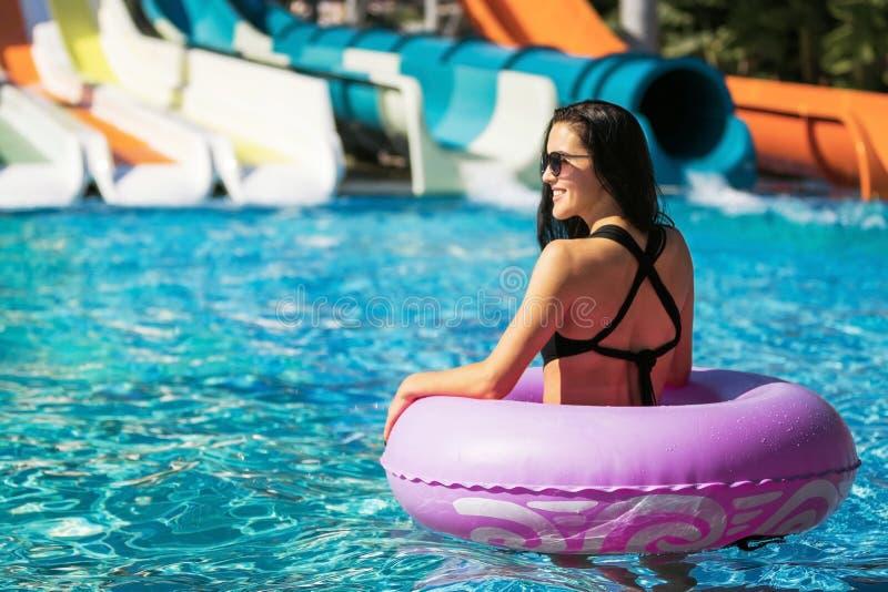 Hübsche Frau im rosa Gummiring im nahen Dia des Pools lizenzfreie stockfotografie