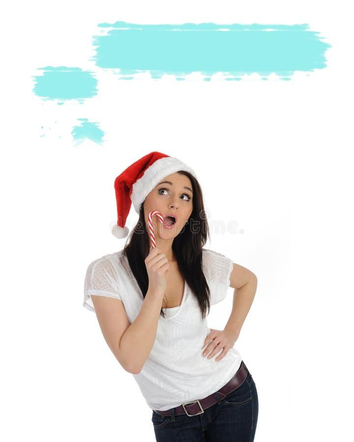 Hübsche Frau im roten Weihnachtshut, der einen Wunsch bildet stockbild