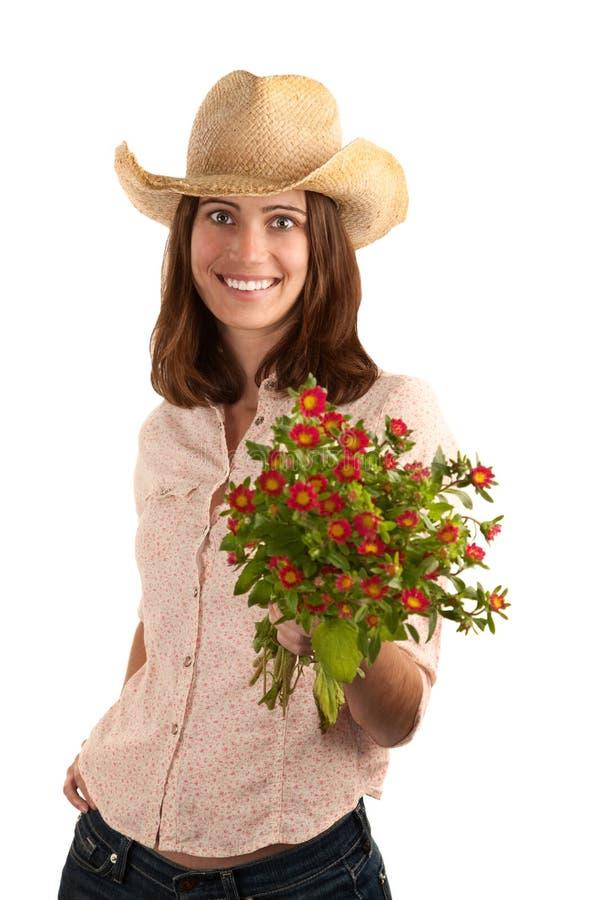 Hübsche Frau mit Cowboyhut und Blumen lizenzfreies stockfoto
