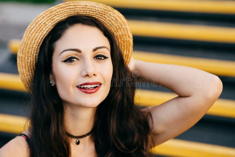 Hübsche Frau mit dem dunklen Haar, den glänzenden Augen und Rot malte die Lippen sicher und mit, die Lächeln tragendem Strohhut d stockfoto