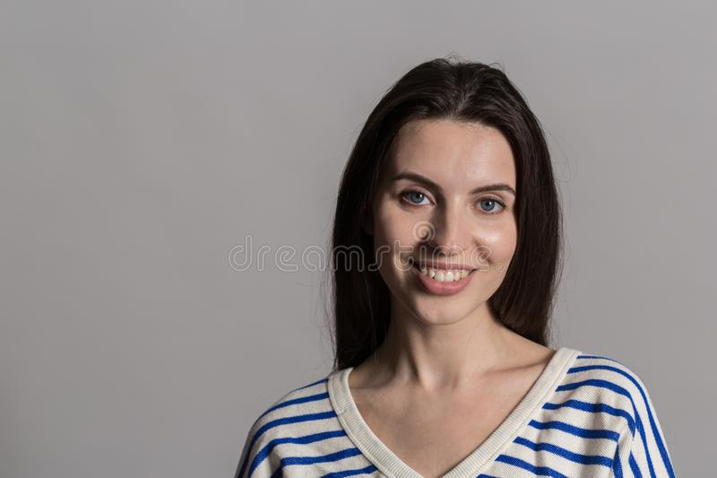 Hübsche Frau mit dem flaumigen Haar, zufällig gekleidet gegen eine graue Studiowand stockfotografie