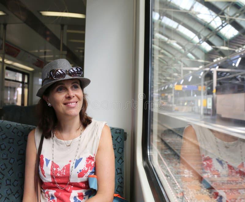 Hübsche Frau mit dem Hut, der im Zug in der Station sitzt lizenzfreie stockfotos