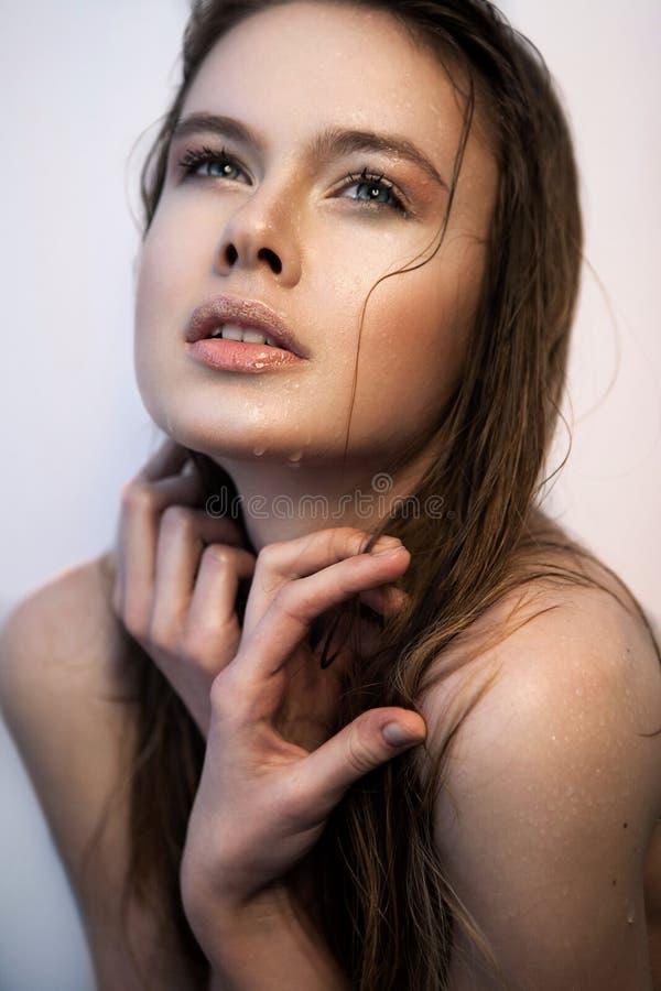 Hübsche Frau mit dem nassen Haar und gekreuzten den Händen, die oben schauen lizenzfreie stockbilder