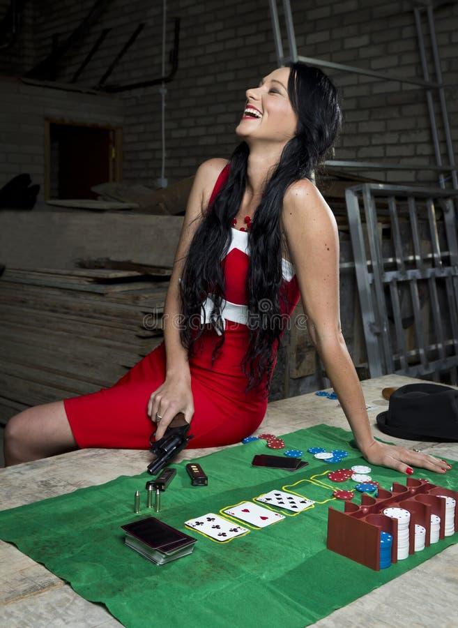 Hübsche Frau mit dem Revolver, der über Schürhakentisch lacht stockfotos
