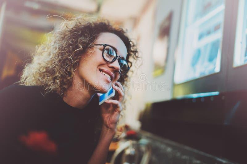 Hübsche Frau mit dem schönen Lächeln, das Anruf über ihren Handy während des Restes in der Kaffeestube macht Bokeh und Aufflacker lizenzfreie stockfotografie