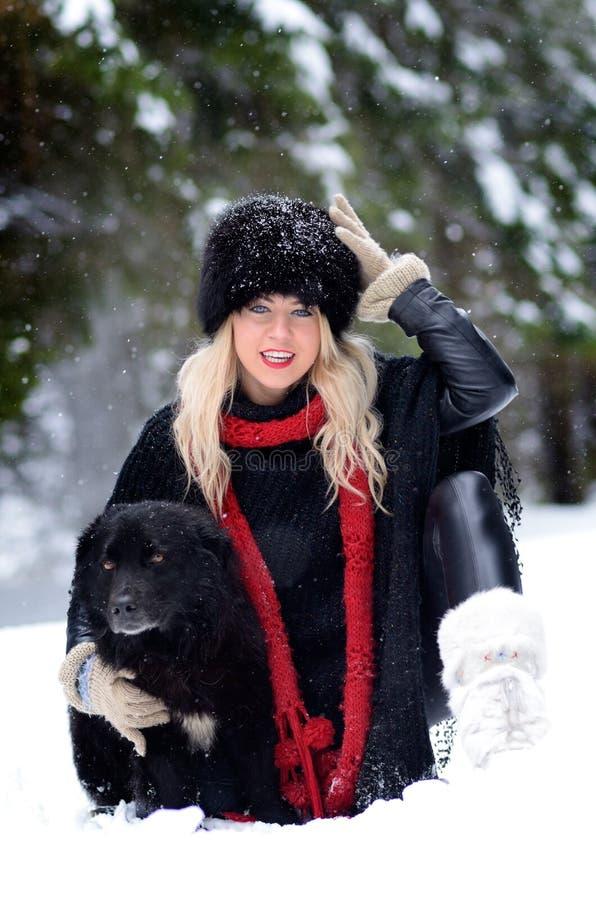 Hübsche Frau mit dem schwarzen Hund im Freien im Winter stockfoto