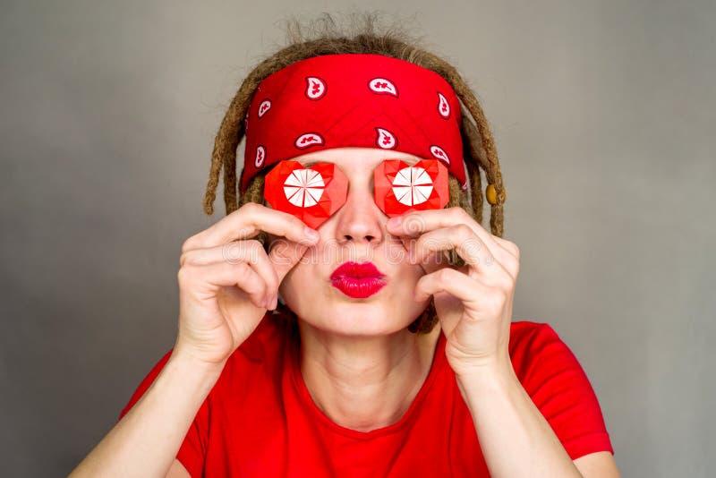 Hübsche Frau mit Dreadlocks mit einem roten Herzen des Origamis, für Valentinsgruß ` s Tag stockfoto