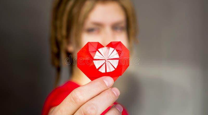 Hübsche Frau mit Dreadlocks mit einem roten Herzen des Origamis, für Valentinsgruß ` s Tag lizenzfreie stockbilder
