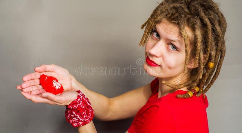 Hübsche Frau mit Dreadlocks mit einem roten Herzen des Origamis in ihren Händen lizenzfreies stockfoto