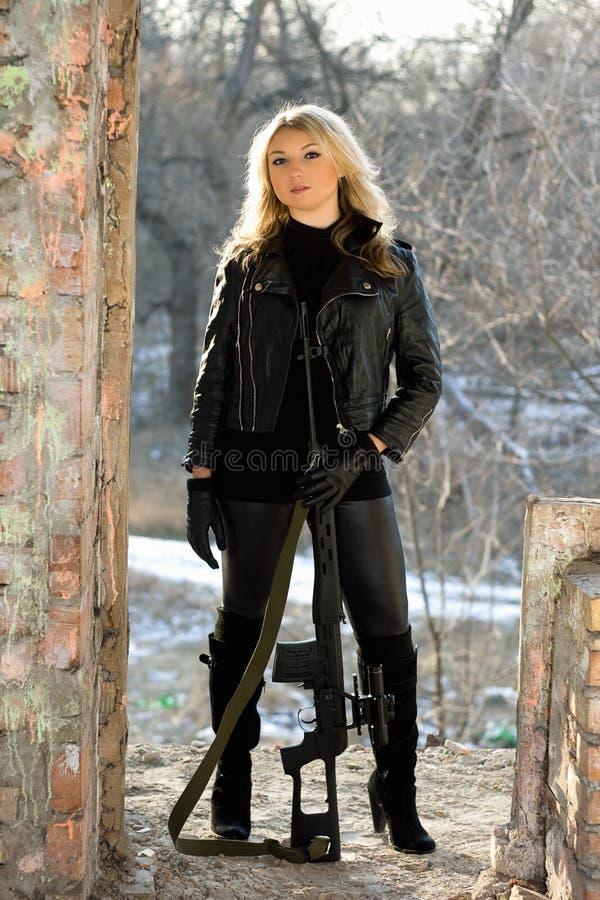 Hübsche Frau mit einem Scharfschützegewehr stockfotografie
