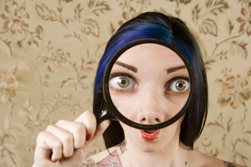Hübsche Frau mit einem Vergrößerungsglas vor h lizenzfreie stockbilder