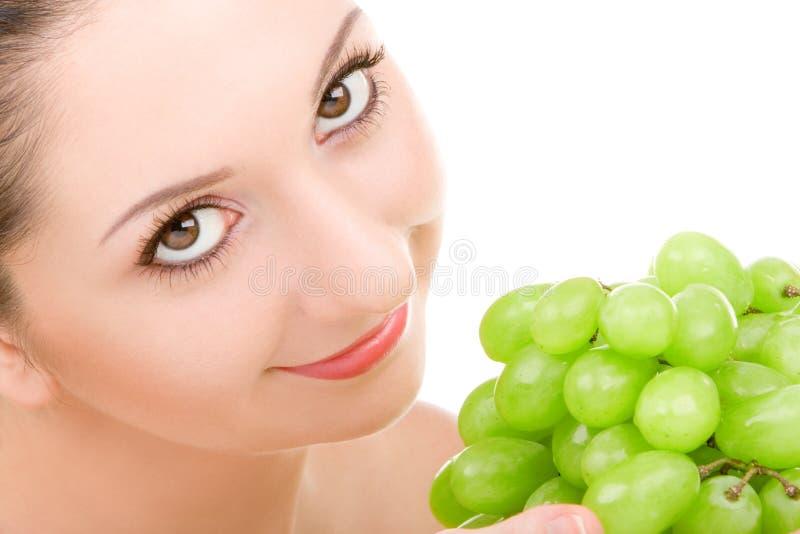 Hübsche Frau mit grüner Traube stockfotografie