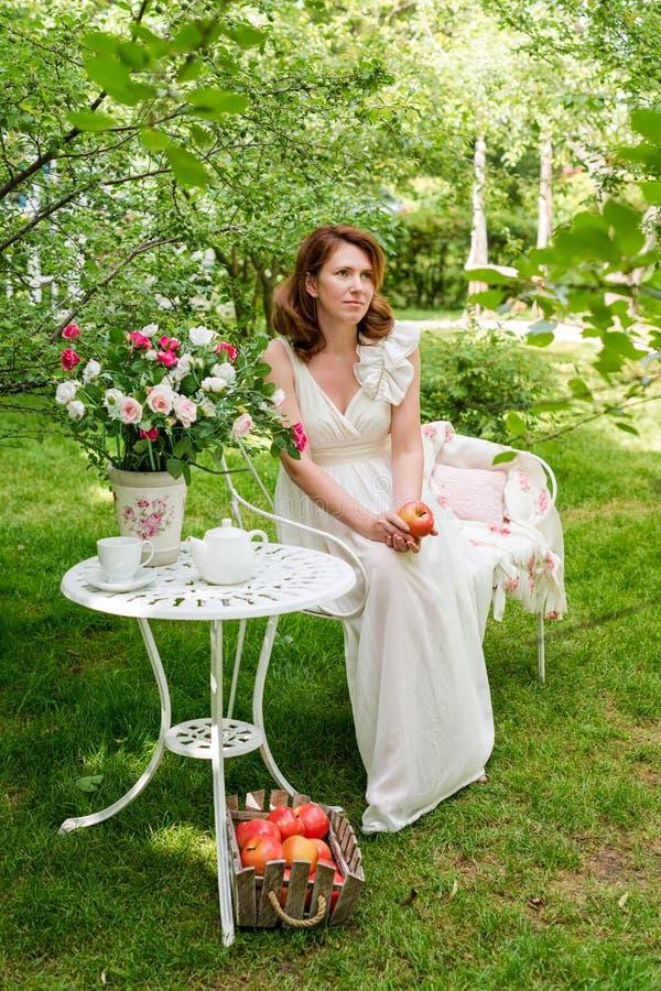 Hübsche Frau mit Kasten Äpfel havig Spaß im Sommergarten Feier im Freien, Teeparty lizenzfreie stockbilder