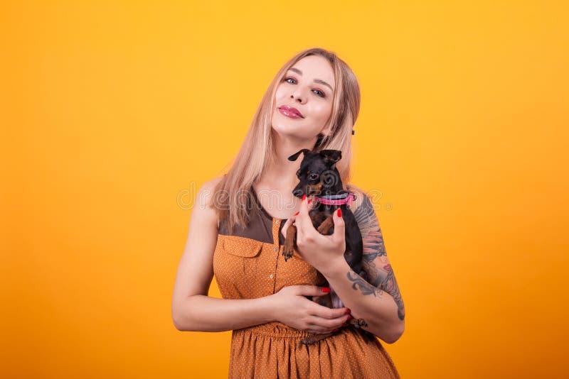 H?bsche Frau mit T?towierung auf ihrer Armholding ihr netter kleiner Hund ?ber gelbem Hintergrund stockfoto