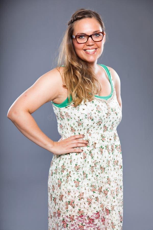 Hübsche Frau mit tragenden Gläsern des langen braunen Haares und Blume kleiden an stockfotos
