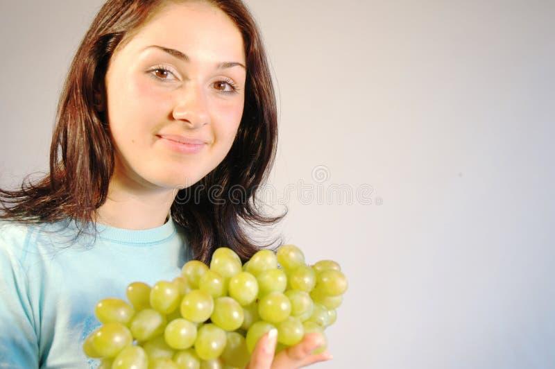 Hübsche Frau mit Trauben lizenzfreies stockbild