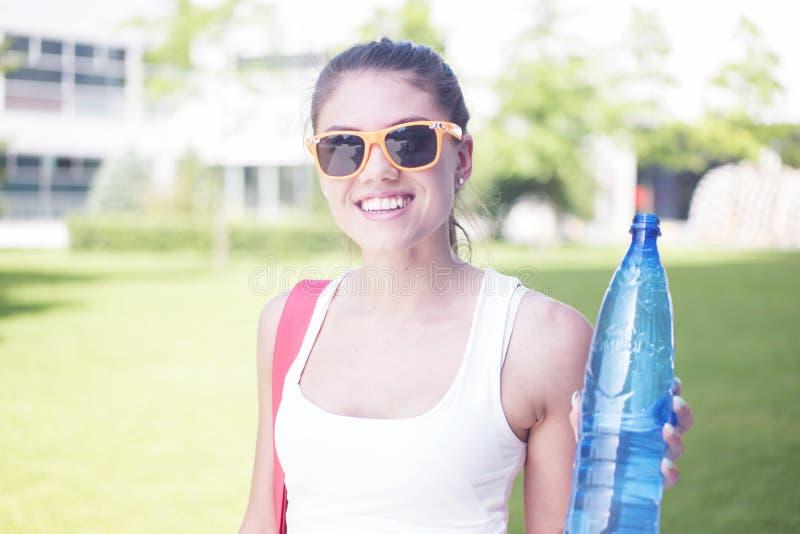 Hübsche Frau am Park, der eine Flasche Wasser hält lizenzfreie stockfotos