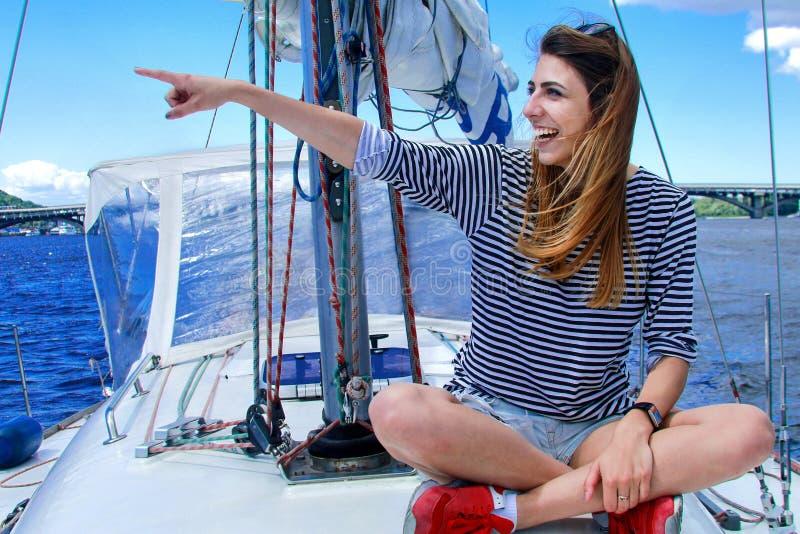 Hübsche Frau sitzt auf einer Yacht und seitlich schaut und Lächeln lizenzfreie stockfotografie