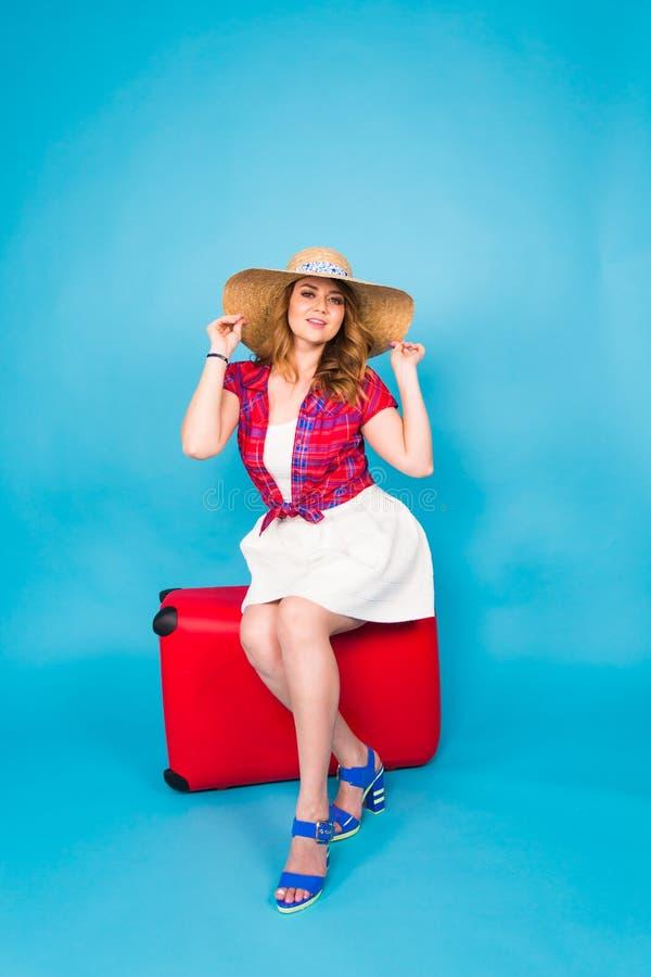 Hübsche Frau sitzt auf rotem Koffer Schönheits-, Mode-, Reise- und Leutekonzept stockfotografie