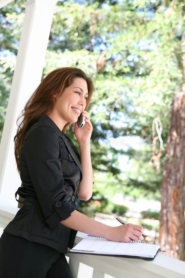 Hübsche Frau am Telefon zu Hause stockbilder