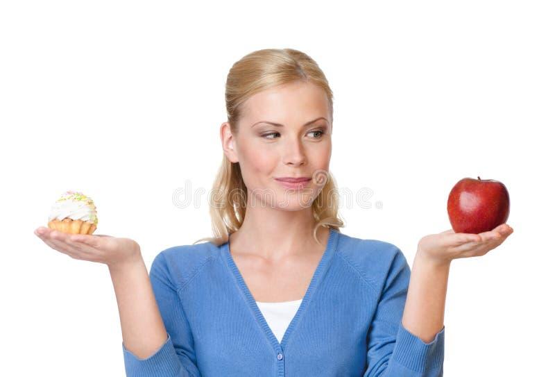 Hübsche Frau trifft eine Wahl zwischen Kuchen und Apfel stockbild