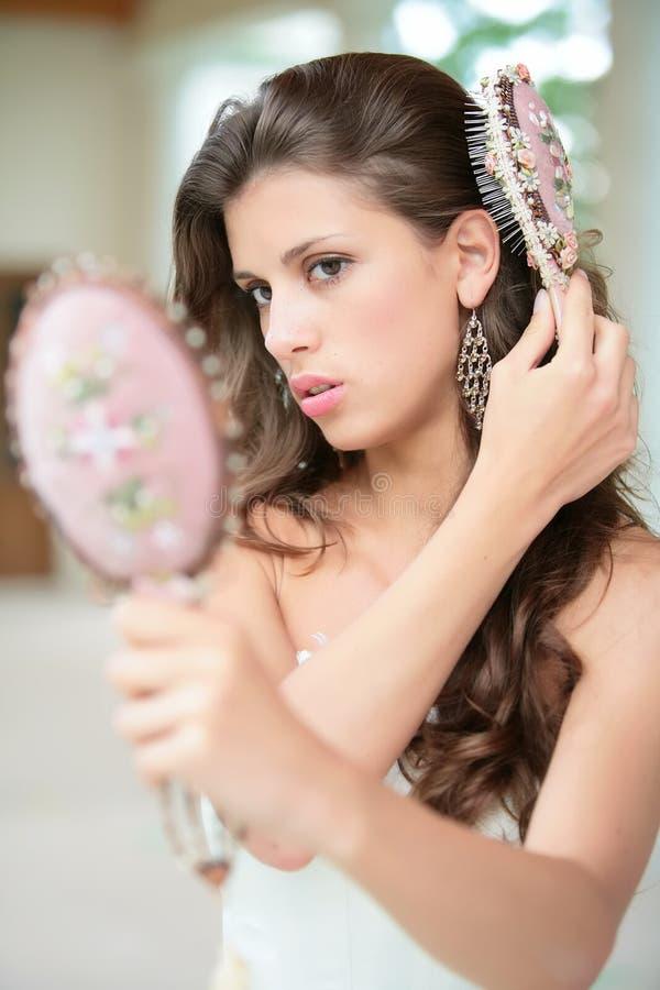 Hübsche Frau tut Frisur lizenzfreie stockbilder