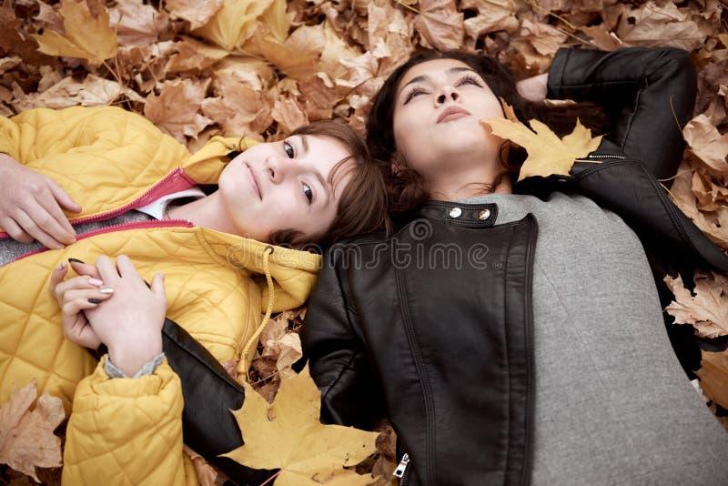 Hübsche Frau und jugendlich Mädchen werfen im Herbstpark auf Sie liegen auf gefallenen Blättern Schöne Landschaft an der Herbstsa stockfoto