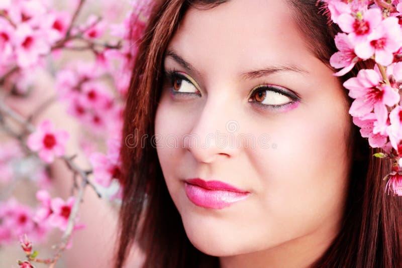 Hübsche Frau unter Pfirsich-Blüten lizenzfreie stockfotos