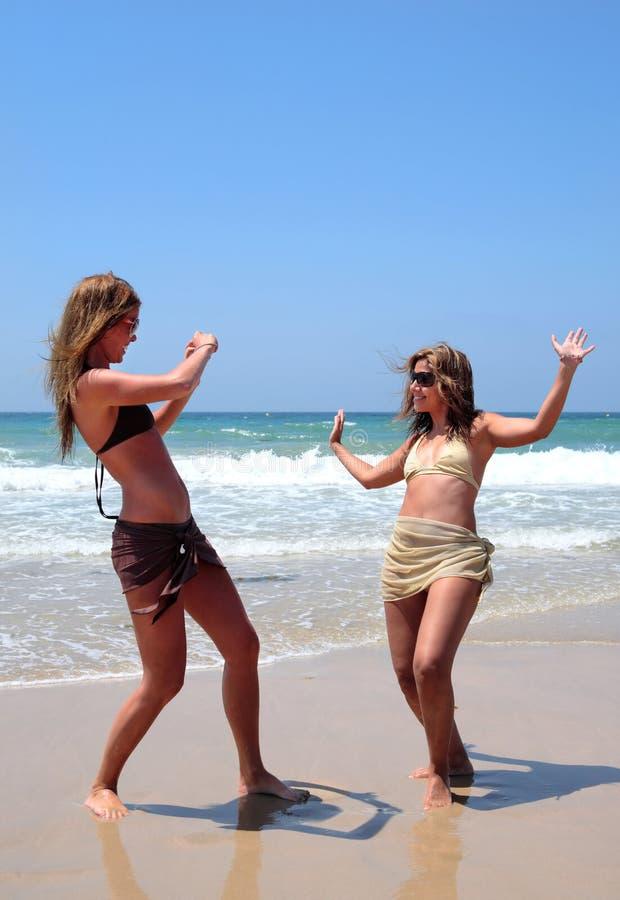 Hübsche Frauen, die auf Strand spielen stockbilder