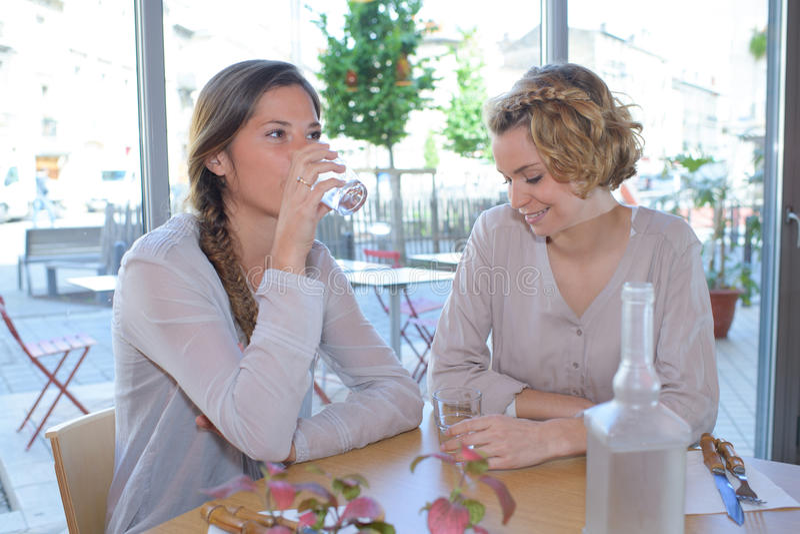 Hübsche Frauen, die im Restaurant zu Mittag essen lizenzfreie stockbilder