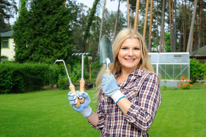 Hübsche Gärtnerfrau mit Gartenarbeithilfsmitteln stockbilder