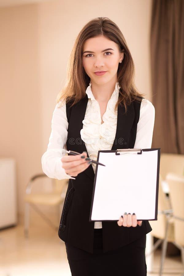 Hübsche Geschäftsfrau, die anbietet, einen Vertrag zu unterzeichnen stockfotografie