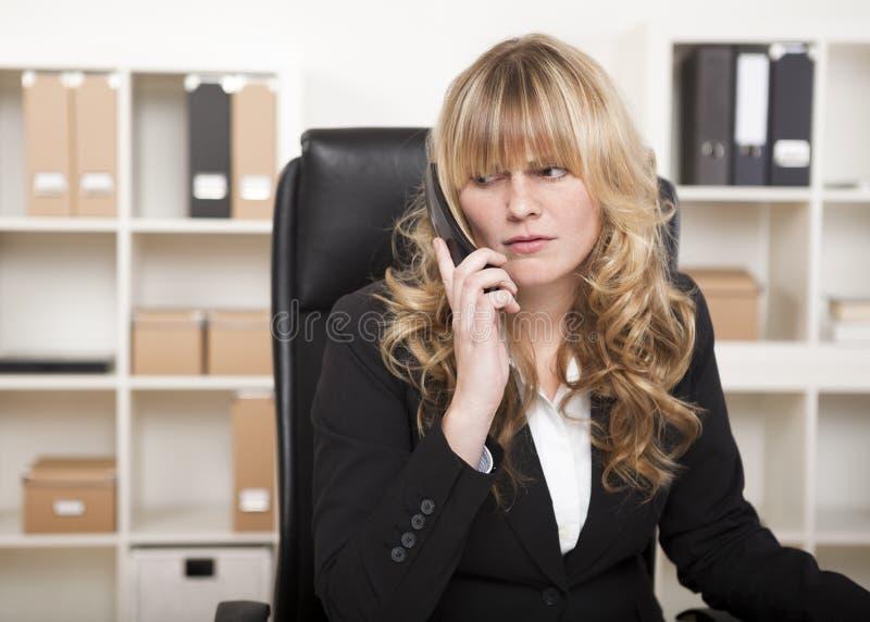Hübsche Geschäftsfrau, die auf einen Telefonanruf hört stockfoto