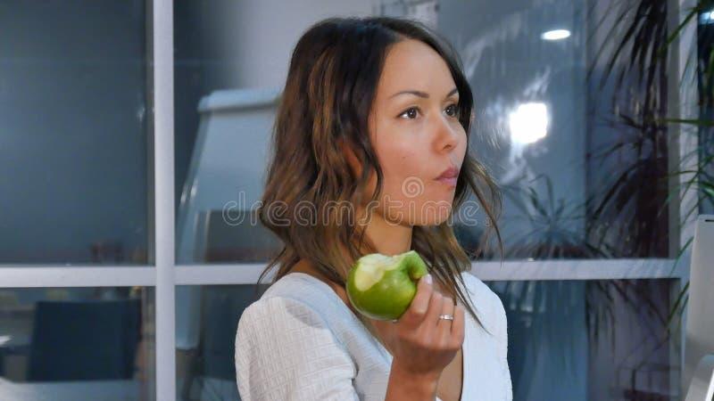 Hübsche Geschäftsfrau, die grünen Apfel im Büro isst lizenzfreies stockbild