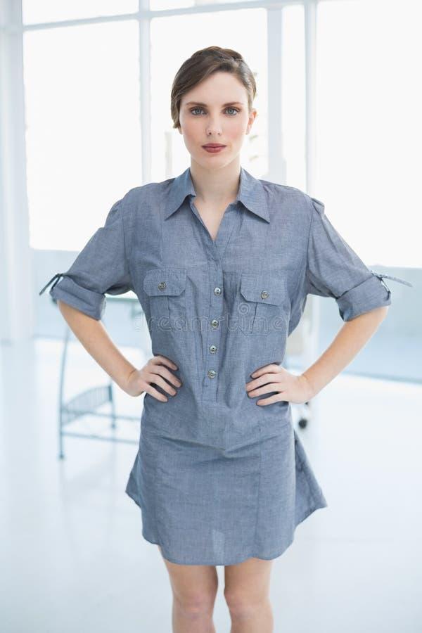Hübsche Geschäftsfrau, die im Büro mit den Händen auf Hüften aufwirft lizenzfreies stockfoto