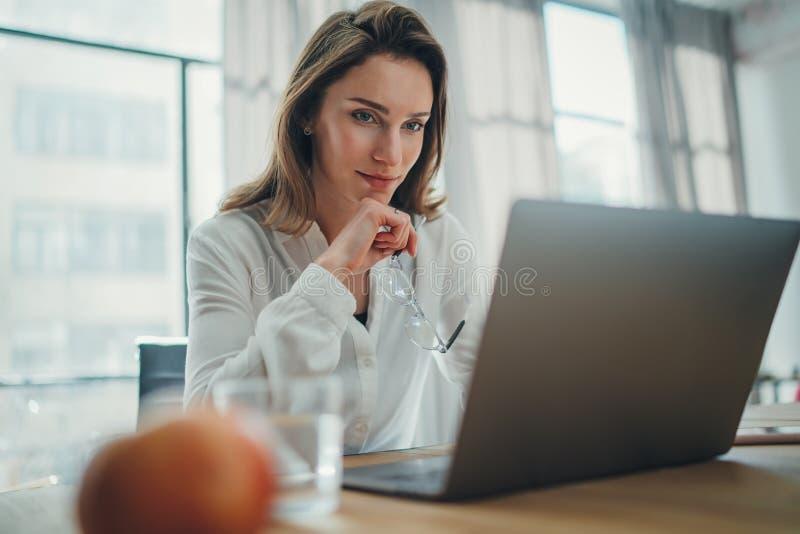 H?bsche Gesch?ftsfrau, die an Laptop an ihrem Arbeitsplatz im modernen B?ro arbeitet Unscharfer Hintergrund lizenzfreies stockbild