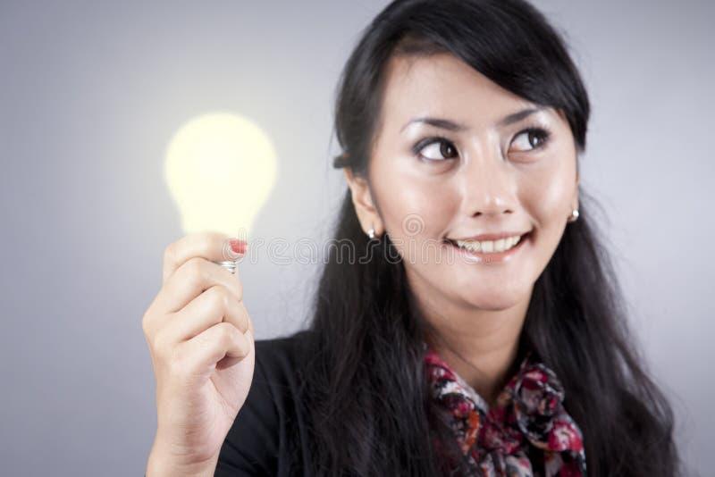Hübsche Geschäftsfrau hält eine Glühlampe an lizenzfreie stockfotografie