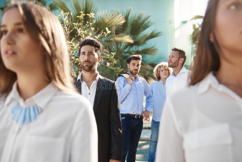 Hübsche Geschäftsmänner, die draußen mit Mitarbeitern stehen stockfotografie
