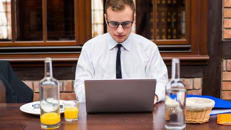 Hübsche Geschäftsmannarbeit am Laptop im Restaurant. stockbild