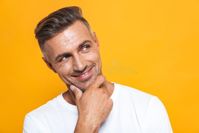 Hübsche glückliche aufgeregte Mannaufstellung lokalisiert über gelbem Wandhintergrund lizenzfreie stockfotos